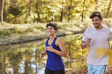Couple jogging on autumnally forest track - SHOF00027
