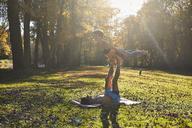 Couple yoga on forest glade, sun light - SHOF00030