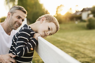 Father looking at smiling boy leaning on fence by grassy field - MASF03170