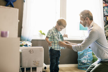 Father dressing up son in brightly lit room at home on sunny day - MASF03176