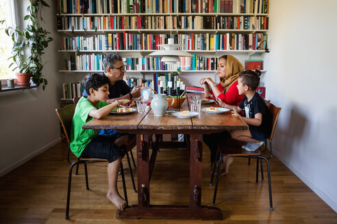 Family having meal at table by bookshelf - MASF03179
