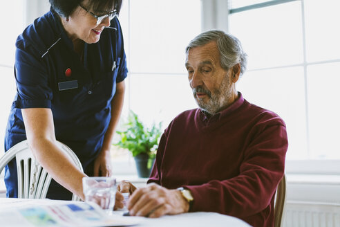 Female caretaker giving medicine to senior man at home - MASF03188