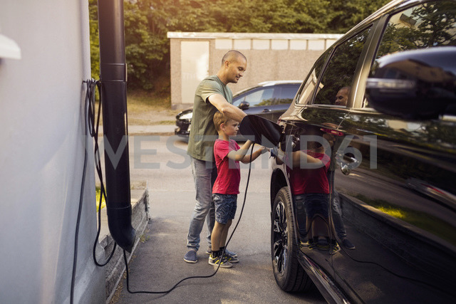 Father and son charging electric car by house - MASF03194