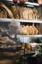 Baker using cash register at bakery - MASF03218