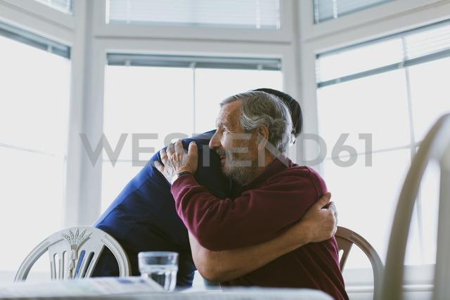 Caretaker embracing senior man at home - MASF03224
