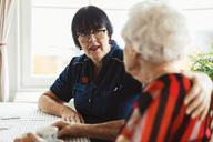 Caretaker talking to senior woman at home - MASF03227