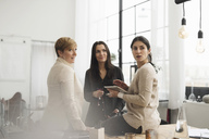 Businesswomen discussing while standing in office - MASF03230