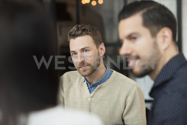 Businessmen looking at woman during meeting in office - MASF03242