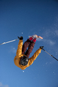 Low angle view of man performing stunt while skiing against clear blue sky - CAVF36646
