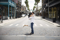 Romantic couple kissing while standing on city street - CAVF36733