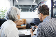 Businessman showing mobile phone to woman in office - CAVF36826