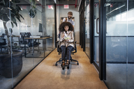 Man pushing woman eating food while sitting on office chair - CAVF36853