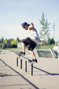 Young man skateboarding on railing - CAVF36997