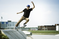 Young man performing stunts on skateboard - CAVF37015