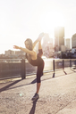 Woman practicing yoga in city during sunrise - CAVF37030