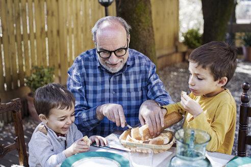 Happy senior man cutting bread loaf for grandsons at yard - CAVF37123