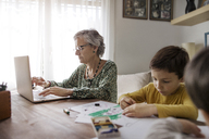 Senior woman using laptop while grandsons making drawings at home - CAVF37132