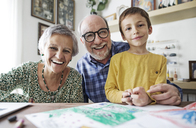 Portrait of happy grandparents with grandson at home - CAVF37138