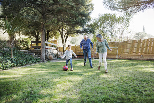 Grandparents playing soccer with grandson at yard - CAVF37144