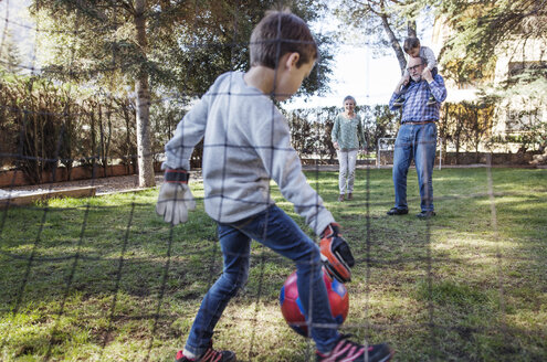 Boy playing soccer with family at yard - CAVF37150
