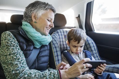 Happy senior woman using smart phone with grandson in car - CAVF37153