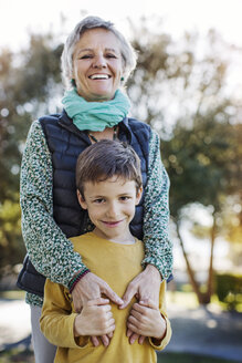 Portrait of happy senior woman standing with grandson in park - CAVF37165