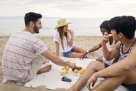 Happy friends eating fruits while sitting on beach - CAVF37198