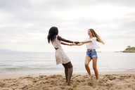 Cheerful female friends playing ring-around-the-rosy on beach - CAVF37207