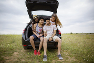 Happy friends using smart phone while sitting in car trunk on field against sky - CAVF37210