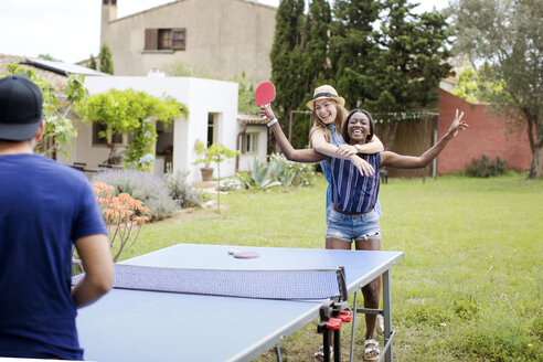 Cheerful women playing table tennis with male friend at yard - CAVF37225