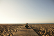 Rear view of woman meditating on footpath at beach against clear sky - CAVF37348