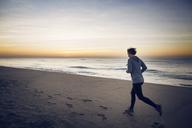 Woman jogging at beach against sky - CAVF37357