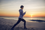 Woman exercising while listening music at beach against sky - CAVF37363