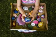 Low section of girl holding painted stones at park - CAVF37450
