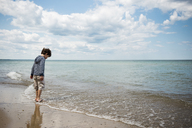 Full length of boy playing in waves at beach against cloudy sky - CAVF37453