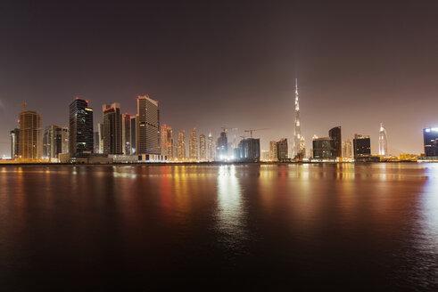 Illuminated cityscape and Dubai creek against clear sky at dusk - CAVF37498