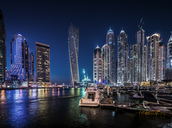 River and illuminated cityscape against blue sky at night - CAVF37501
