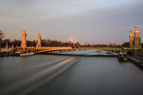 Pont Alexandre III over Seine River against sky during sunset - CAVF37531