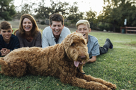 Happy family with Irish Wolfhound lying on grassy field at park - CAVF37588