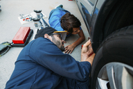 High angle view of serious father teaching son to repair car at driveway - CAVF37615