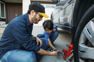 Father teaching son to use car jack at driveway - CAVF37618