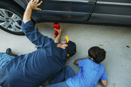High angle view of father teaching son to use car jack at driveway - CAVF37621