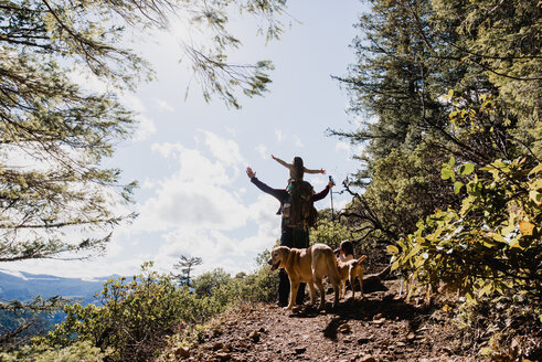 Male hiker carrying daughter while standing by dogs on mountain against sky - CAVF37630