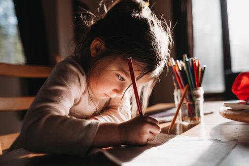 Girl drawing with colored pencil on paper while sitting at table - CAVF37636
