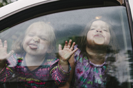 Playful sisters making faces while traveling in car seen through window - CAVF37663
