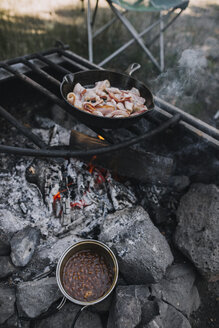 High angle view of bacon in skillet being cooked on open fire at campsite - CAVF37690