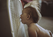 Shirtless baby boy with mouth open enjoying breeze from air conditioner at home - CAVF37714