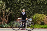 Portrait of businesswoman standing with bicycle against plants - CAVF37765