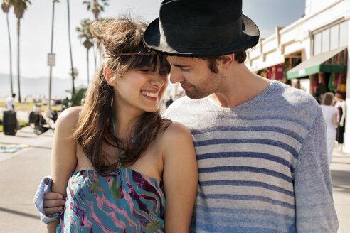 Loving man looking at cheerful woman on sidewalk - CAVF37768