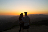 Rear view of couple standing on mountain against sky during sunset - CAVF37807